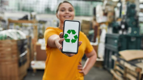 Selective focus on smartphone screen with green recycling sign in hand of happy caucasian young girl working on garbage station, widescreen. Waste sorting and recycling concept